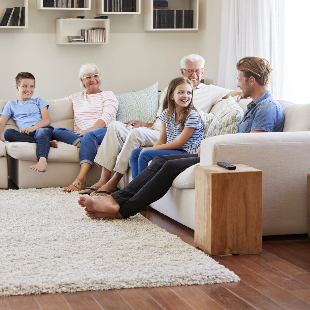 Family get together in living room | Shans Carpets And Fine Flooring Inc